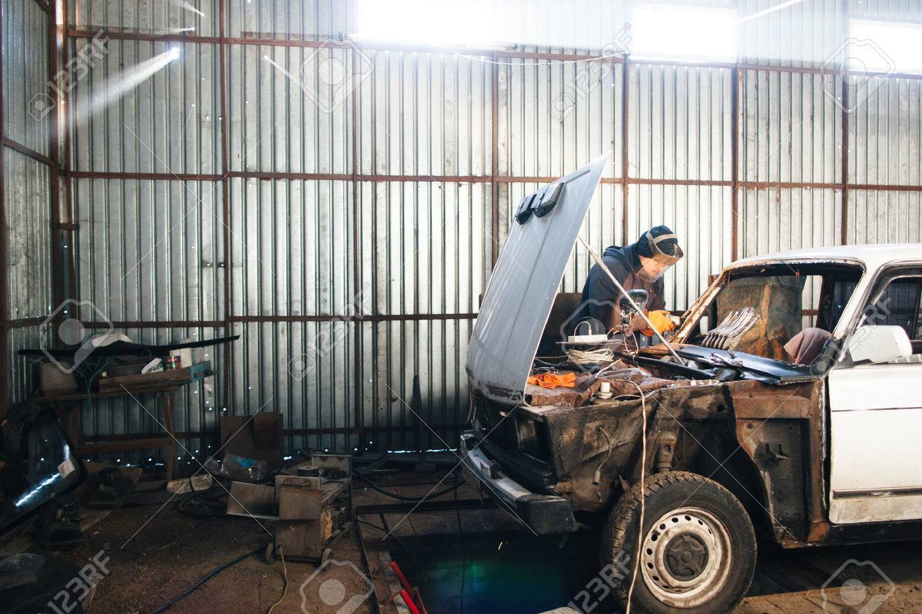 Service station for old damaged automobile. Bodywork and restore body and  engine compartment. Workshop