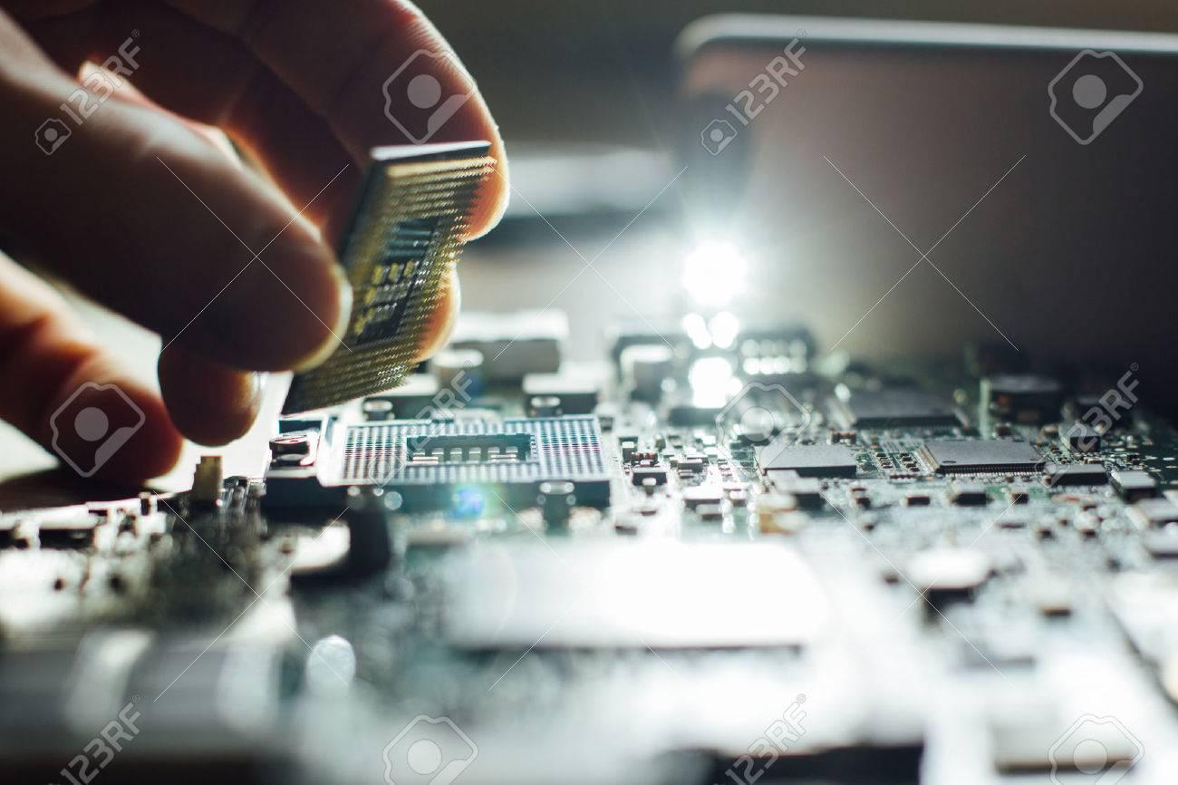 Technician plug in CPU microprocessor to motherboard socket. Workshop background - 54302124