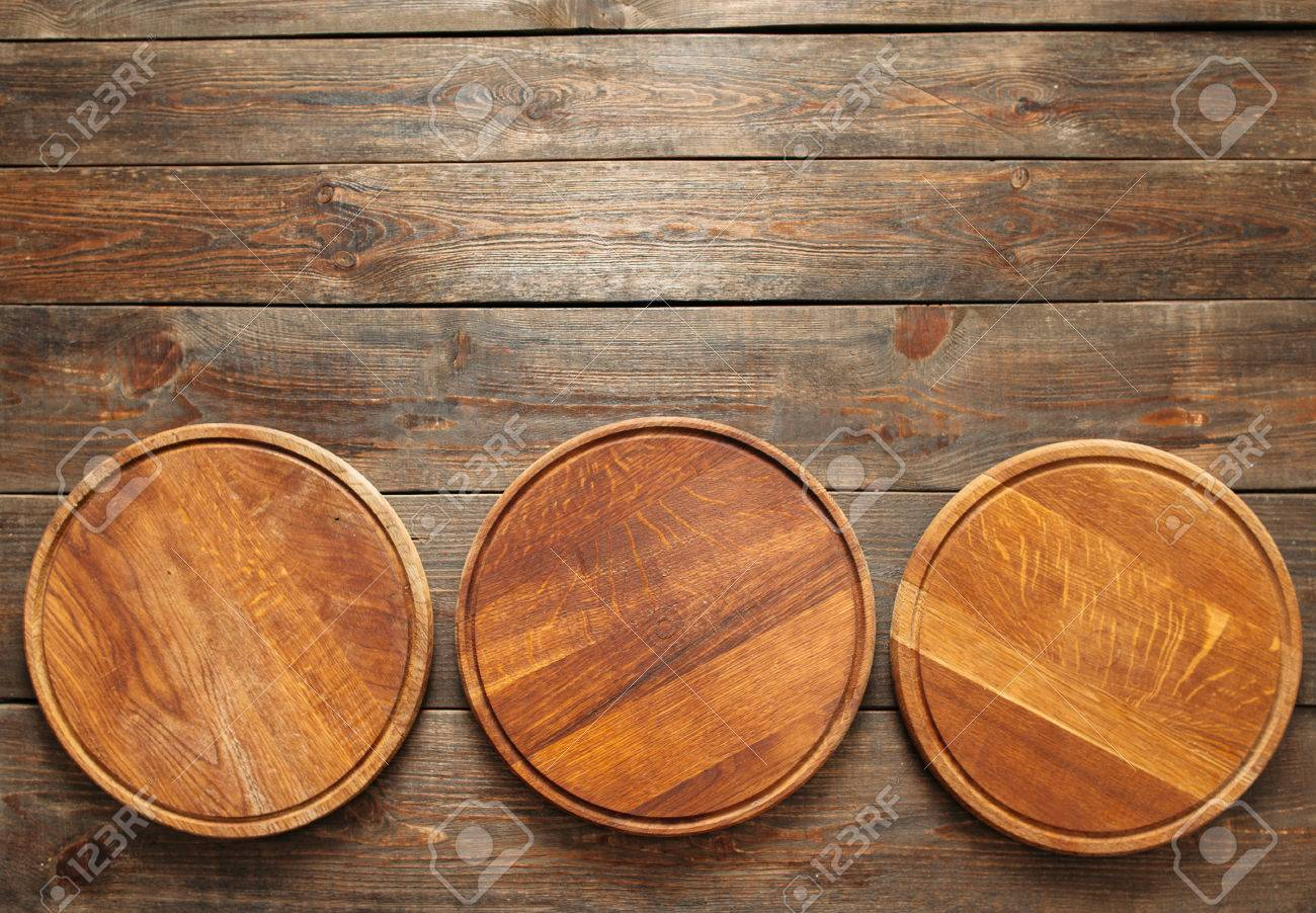 Stock Photo - Three empty wooden pizza plates lie on the wooden table at the bottom of the picture. Copy space. Horizontal line. & Three Empty Wooden Pizza Plates Lie On The Wooden Table At The ...