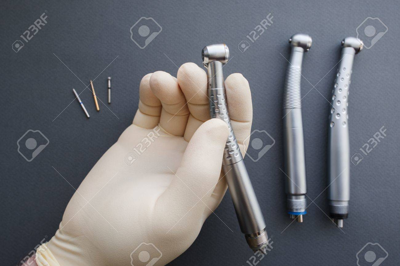 hand of dentist in latex protective gloves holding dental drill