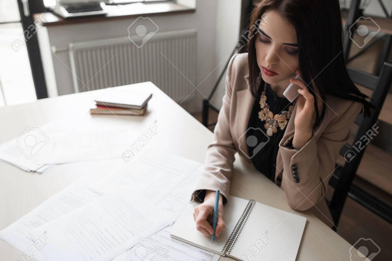 Belle fille de bureau à usage formel parlant au téléphone mobile et