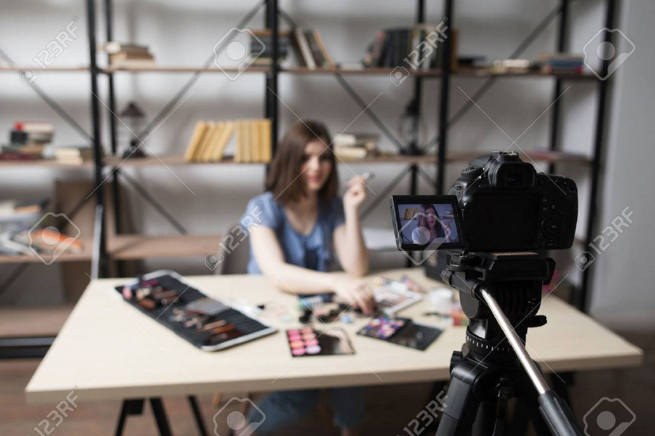 Female vlogger recording video at home. Close-up of camera screen with young blogger face picture. Fashion, beauty, technology concept - 63000196