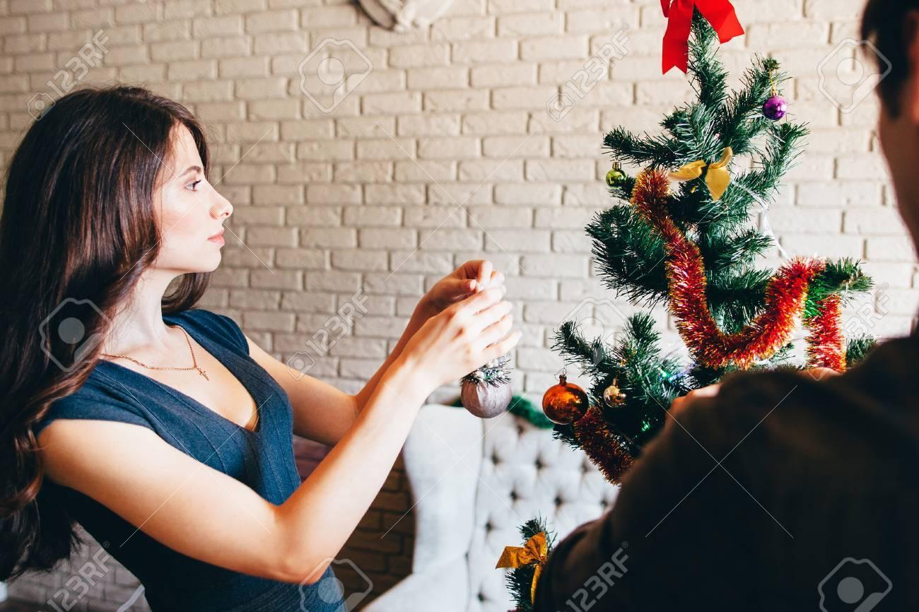 jeune femme séduisante, décorer le sapin de noël. belle brune