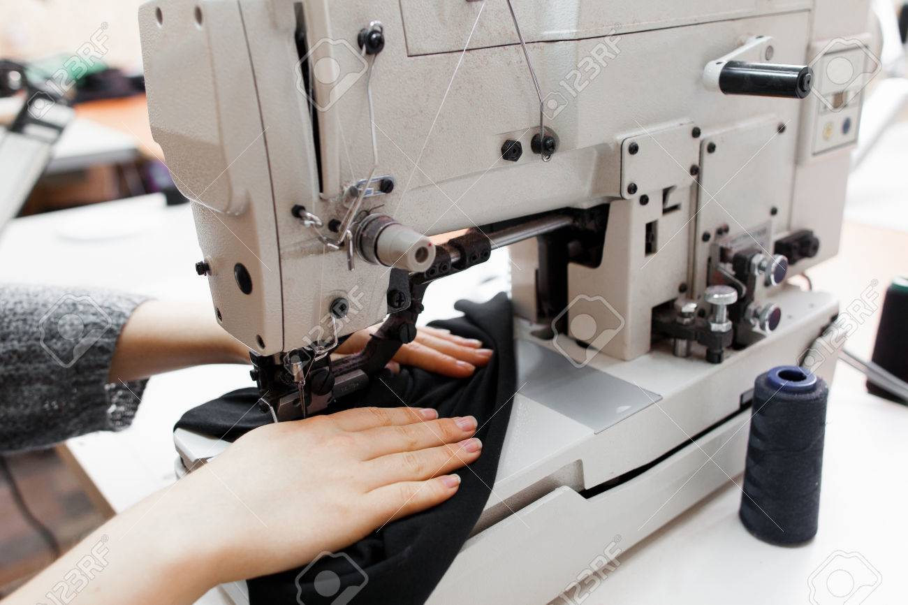 Woman stitching dark fabric on sewing machine. Close-up of seamstress hands making clothes on professional equipment. Garment industry, designer atelier, tailoring process concept - 66785688