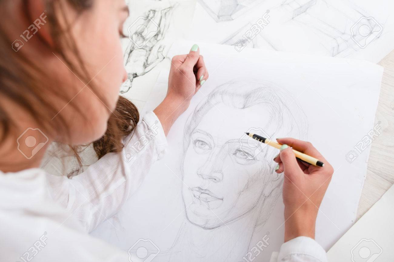 Artist drawing pencil portrait close-up. Woman painter creating picture of woman on big whatman. Art, talent, craft, hobby, occupation concept - 67217671