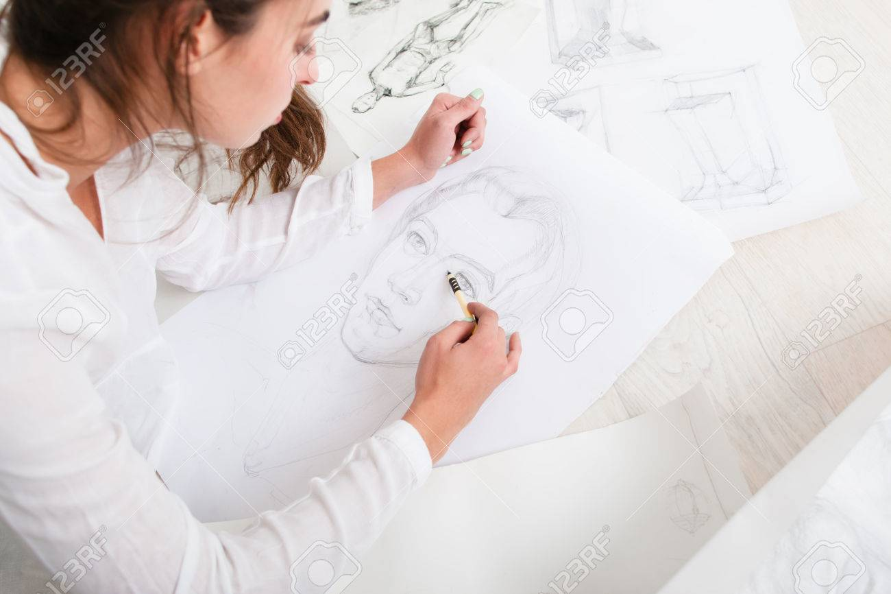Artist finishing human pencil portrait on floor top view on