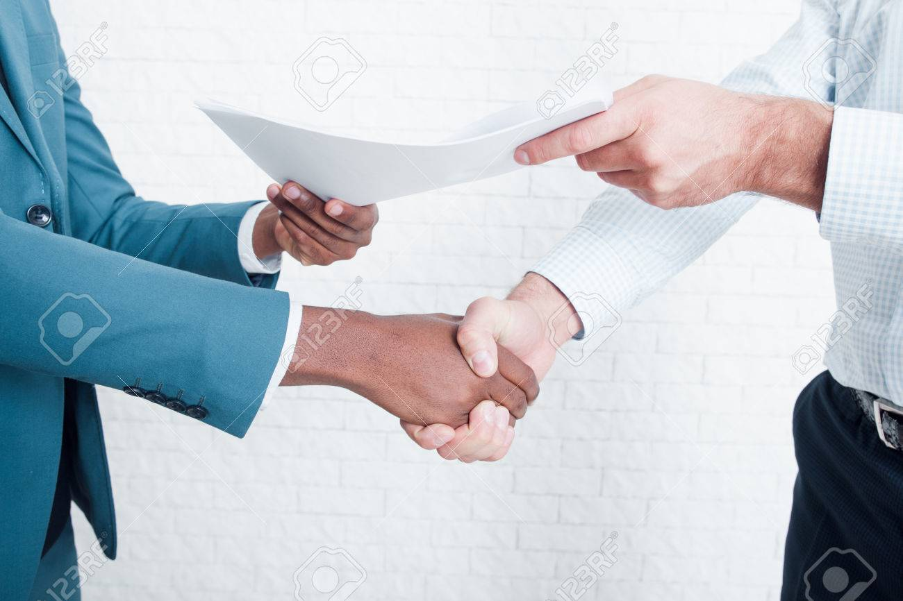 Handshake in office after making deal. Two owners of business signed contract about interracial cooperation. - 74635360