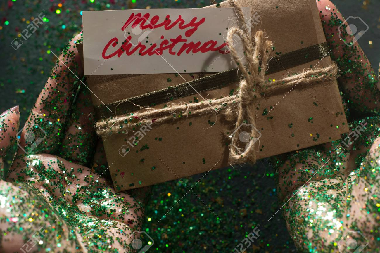 Festive backdrop of Christmas present. Gift bag with greeting memo and  holiday sparkles holding in