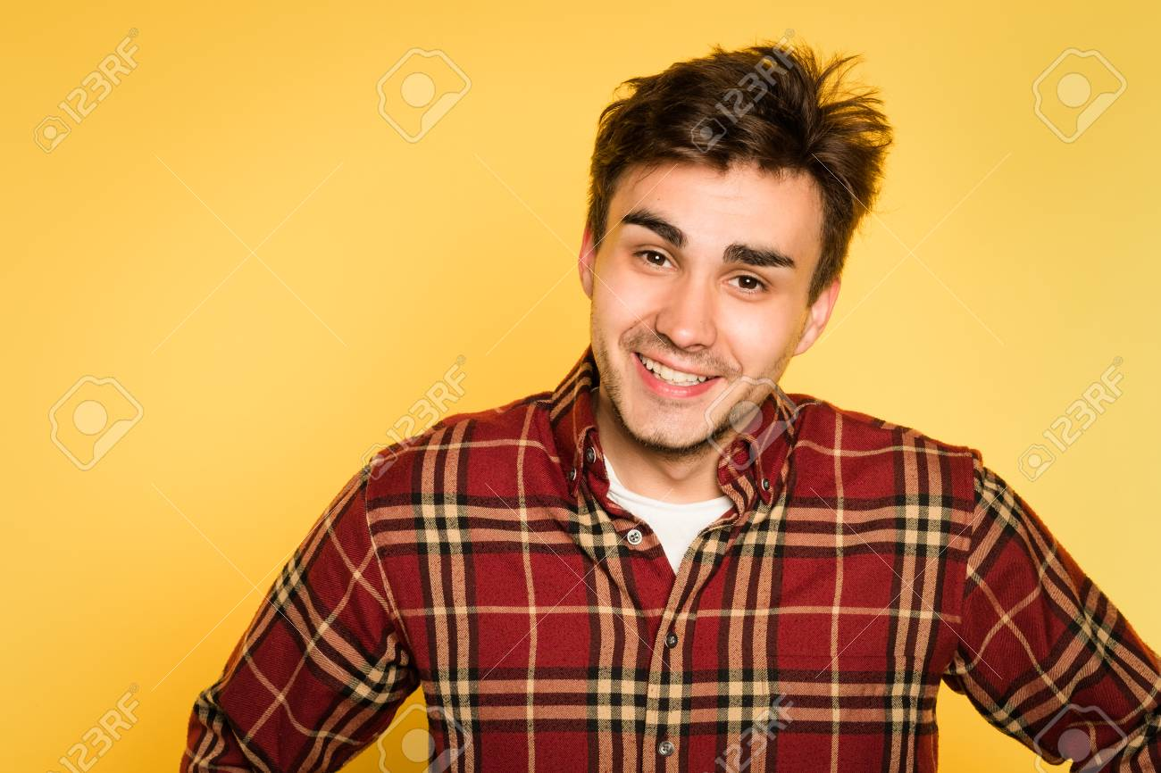 13165266 Ruffled disheveled laid back man smiling. portrait of a young handsome  brunet guy on yellow