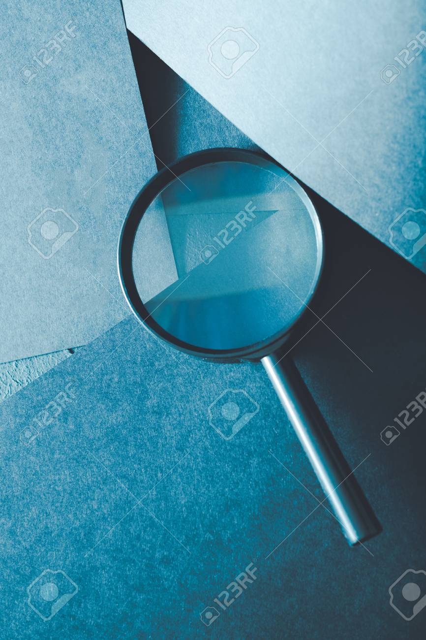 magnifying glass. science research exploration and scrutiny concept. loupe on layered blue paper background. - 109414990