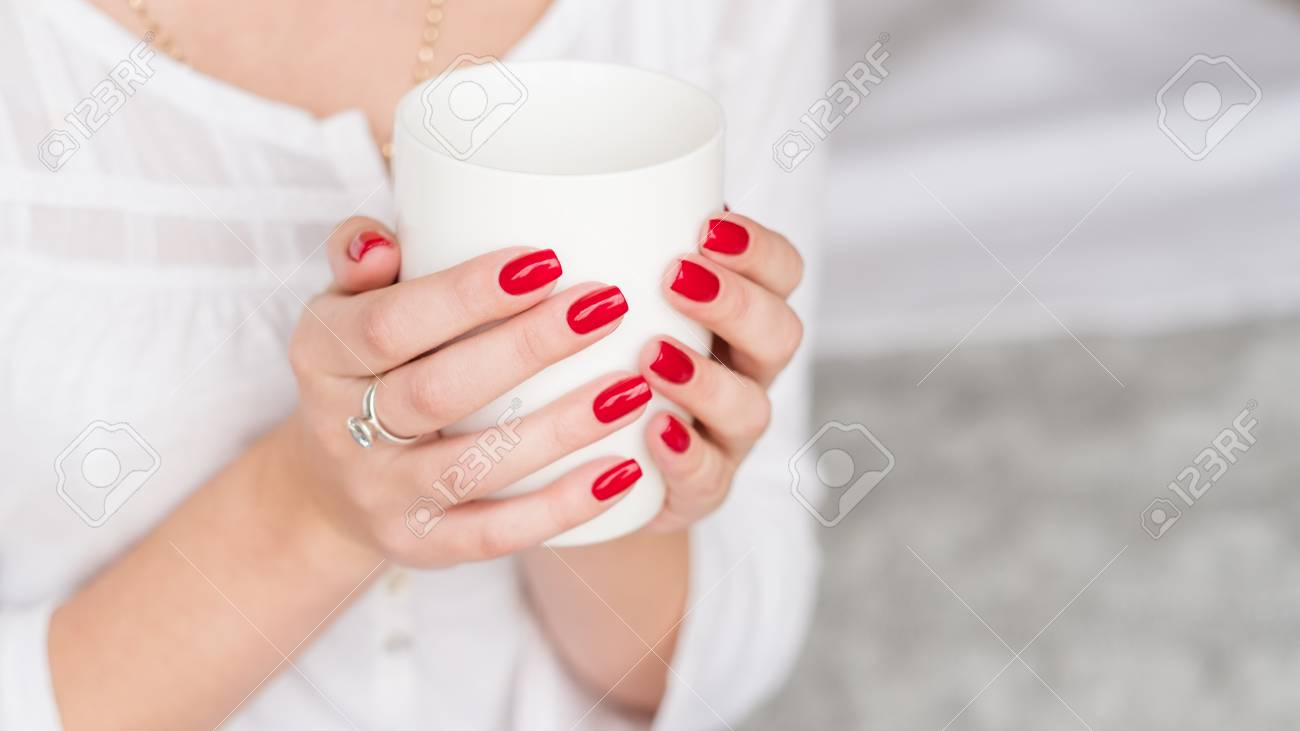 Wake up beverage. Woman manicured hands with white cup of hot morning drink. - 117037842