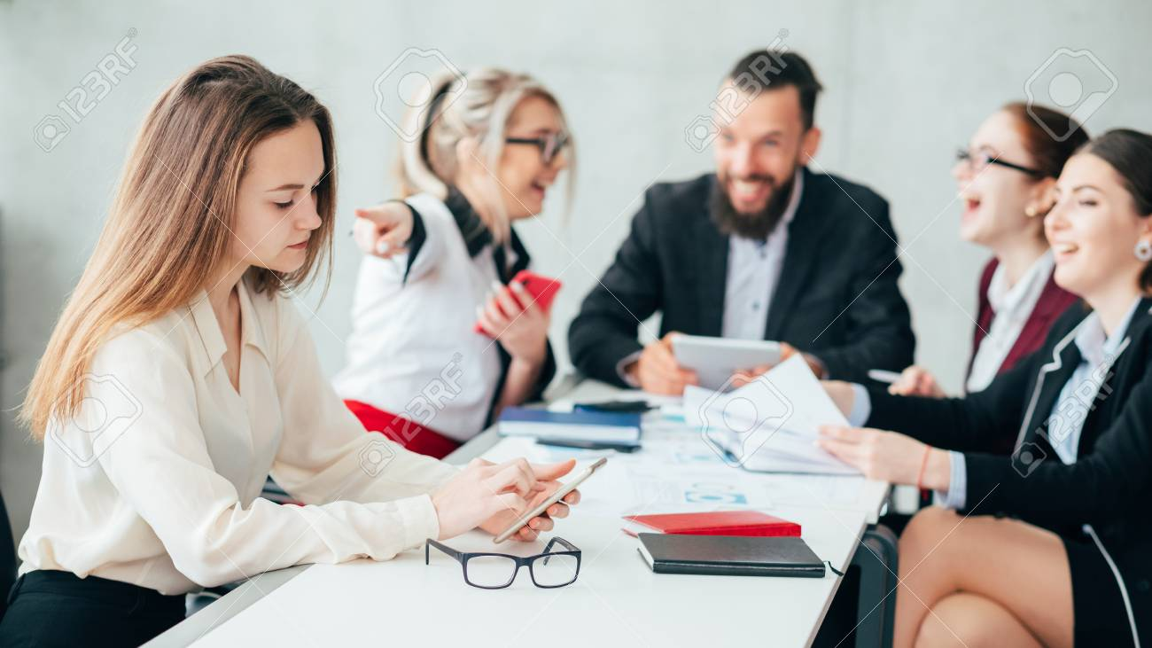 Corporate employees. Bullying and mocking. Business team meeting. Woman point finger at upset colleague checking smartphone. - 117540011