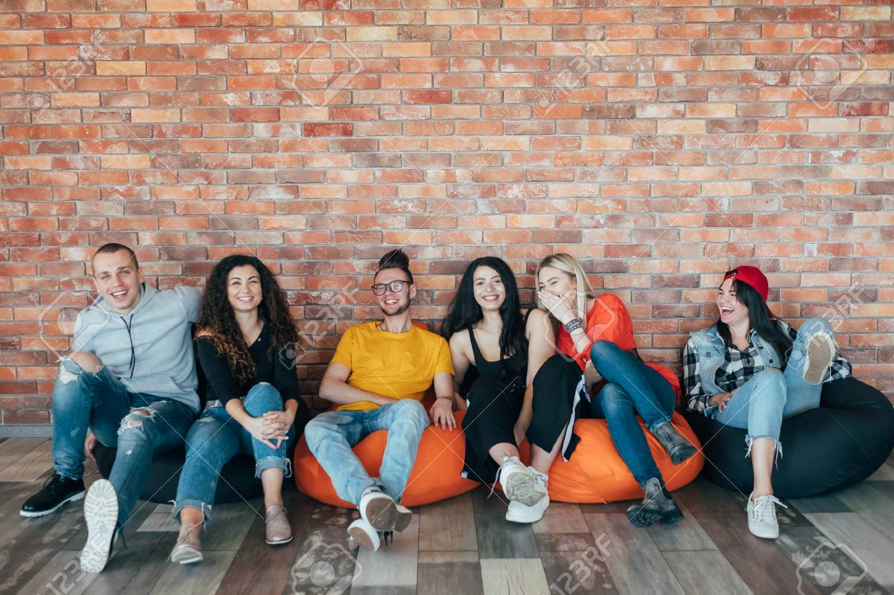 Millennials chilling out in leisure zone after successful hard working day. Young people sitting in cushion chair, laughing. - 121283471