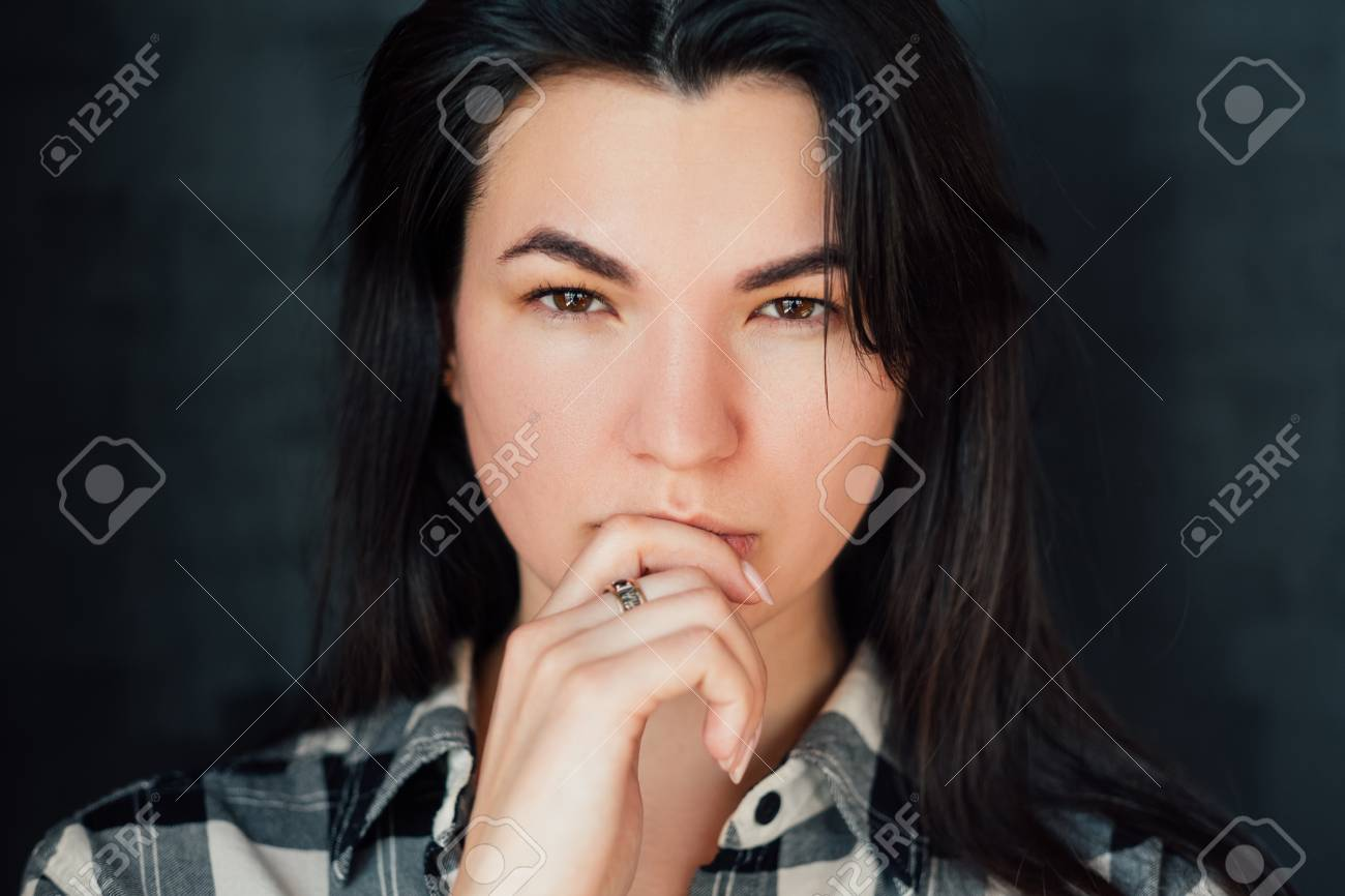 Young woman portrait. Intense look. Fixed gaze. Speculation. Thoughtful brunette looking at camera. Decision making time - 121284018