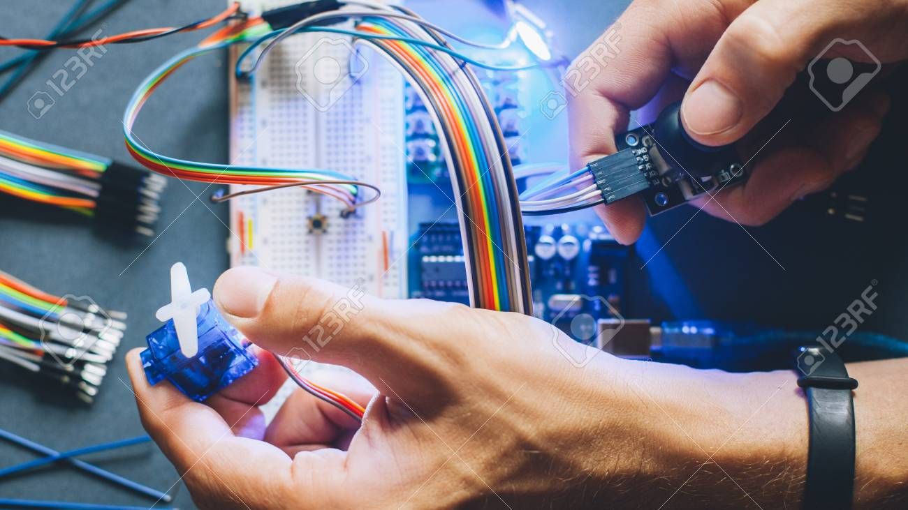 Engineer inventing prototype. Robotic electronic module construction. Microcontroller programming. Hands working with electrical sensor. - 121284361