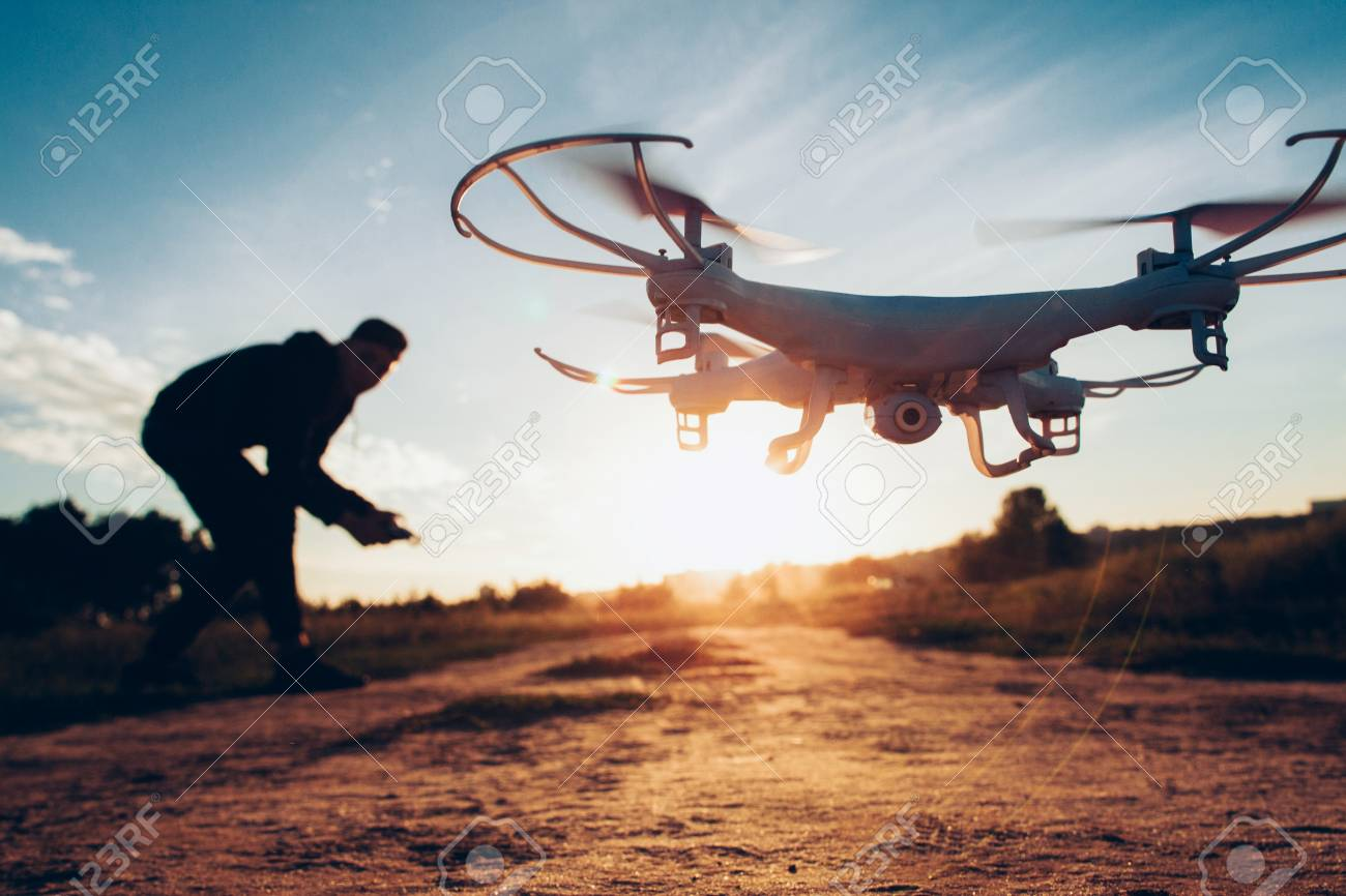 Drone trends and innovations. Modern hobby and leisure. Closeup of camera quadcopter controlled remotely by guy over blur sunset. - 121261053