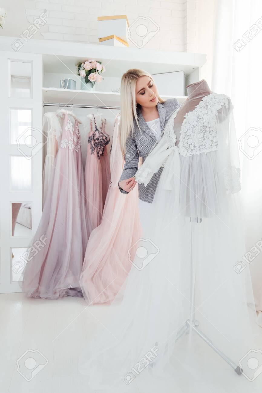 Luxury boutique. Personal shopper performing designer evening gown from latest collection. Modern showroom interior. - 123886515