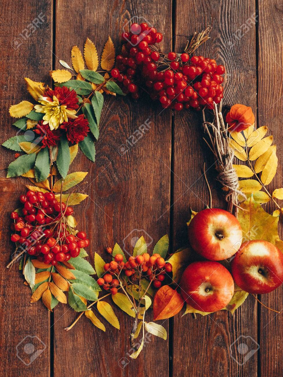 Autumn wrench decor. Colorful fall plants, leaves arranged in round frame on brown wooden background. Copy space. - 125608524