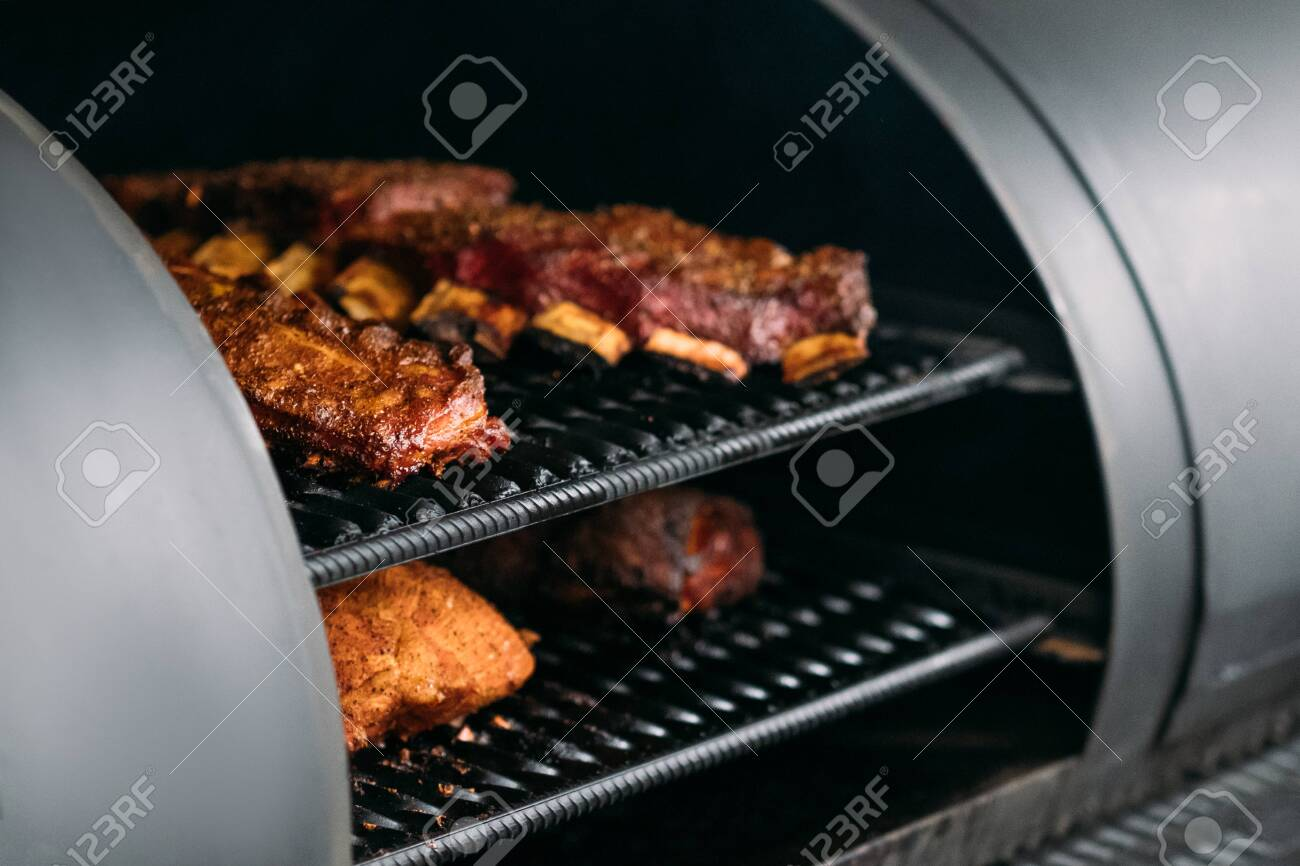 Professional kitchen appliance. Poultry, beef and pork meat, ribs cooked in BBQ smoker. - 129911729