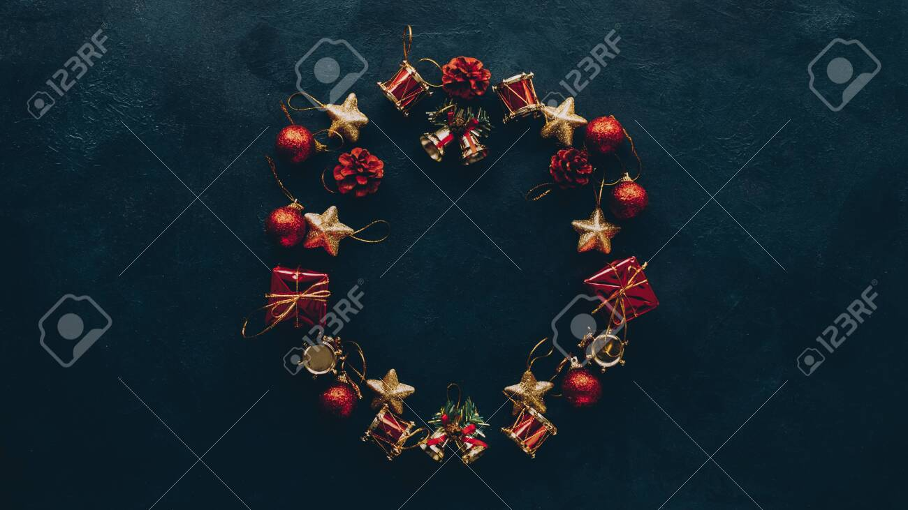 New Year greeting card. Top view of Christmas wreath frame from ornaments on dark teal blue background. Copy space. - 129911486
