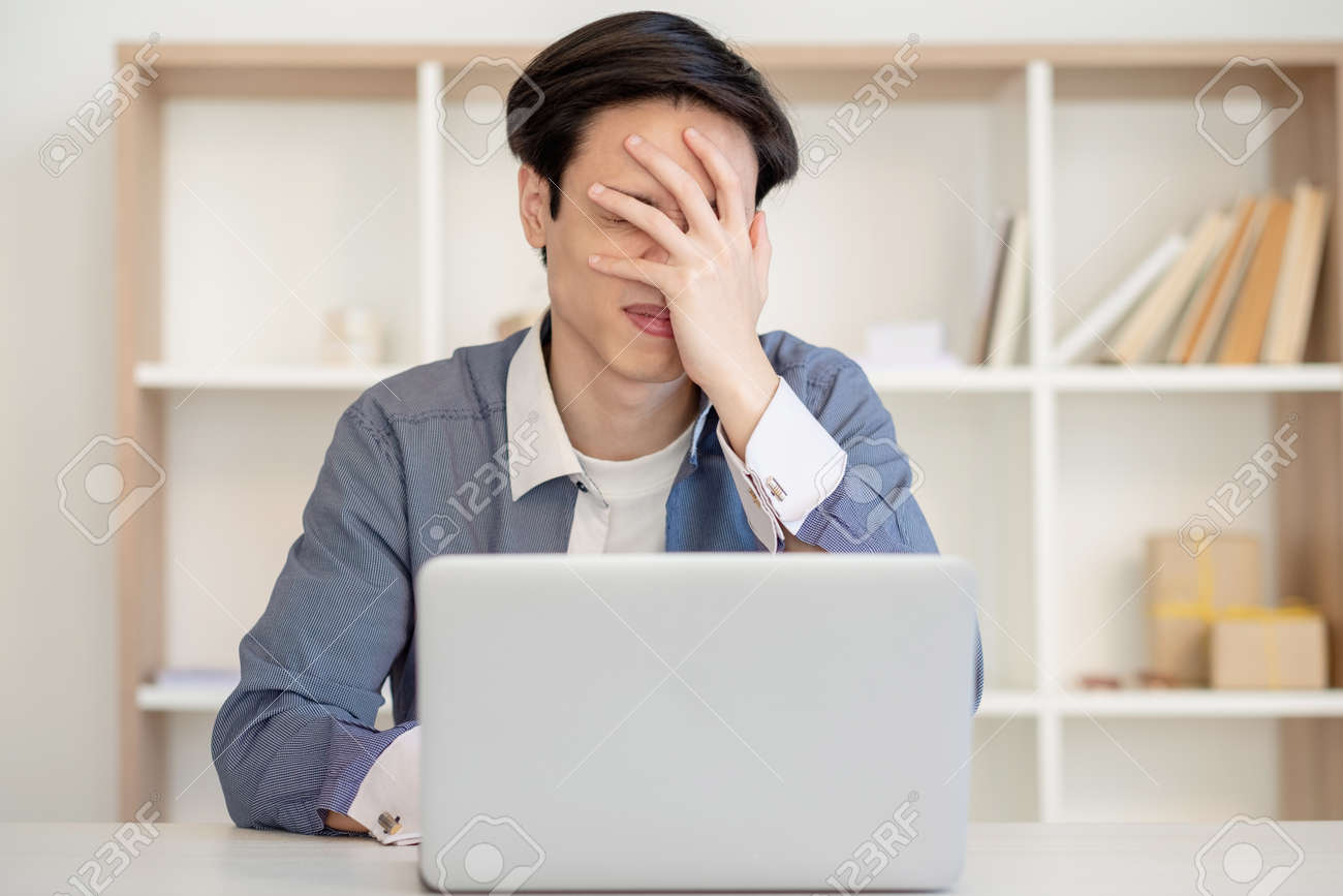 Desperate employee. Task failure. Remote job. Startup crash. Frustrated stressed asian man working with laptop showing facepalm gesture at light home office. - 158142686