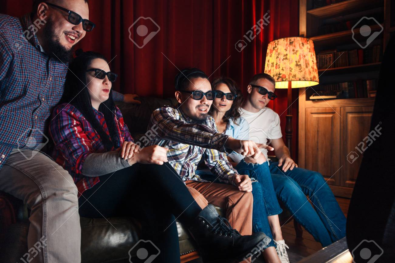 5e7b56b94ac5 Company of five young friends excited watch movie in 3d glasses at home on  couch.