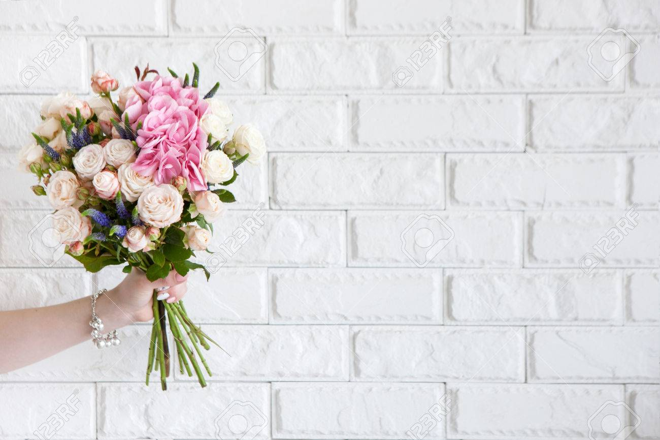 Female Hand Show Bouquet With Rose Flowers On White Brick Background ...
