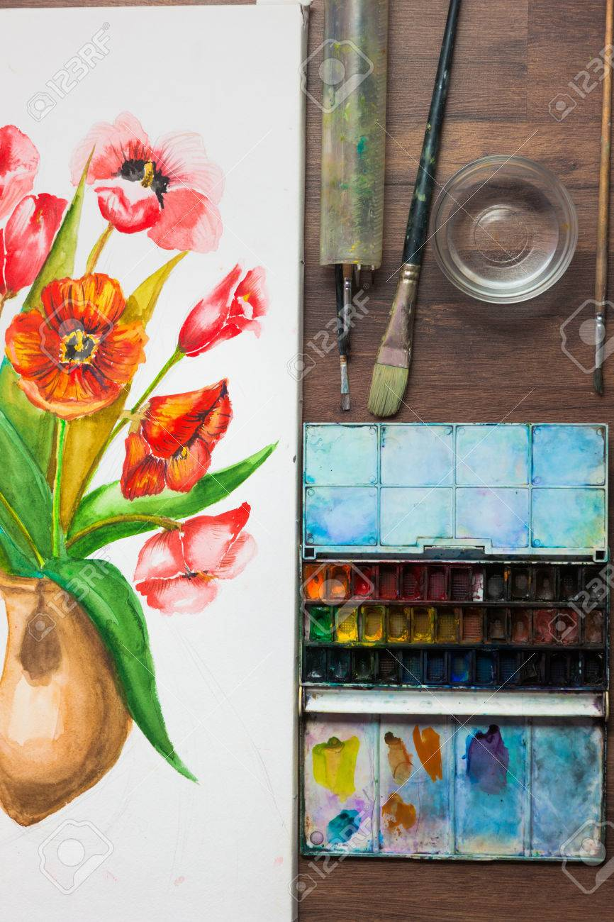 Watercolor flowers and set of painters tools top view  Workplace