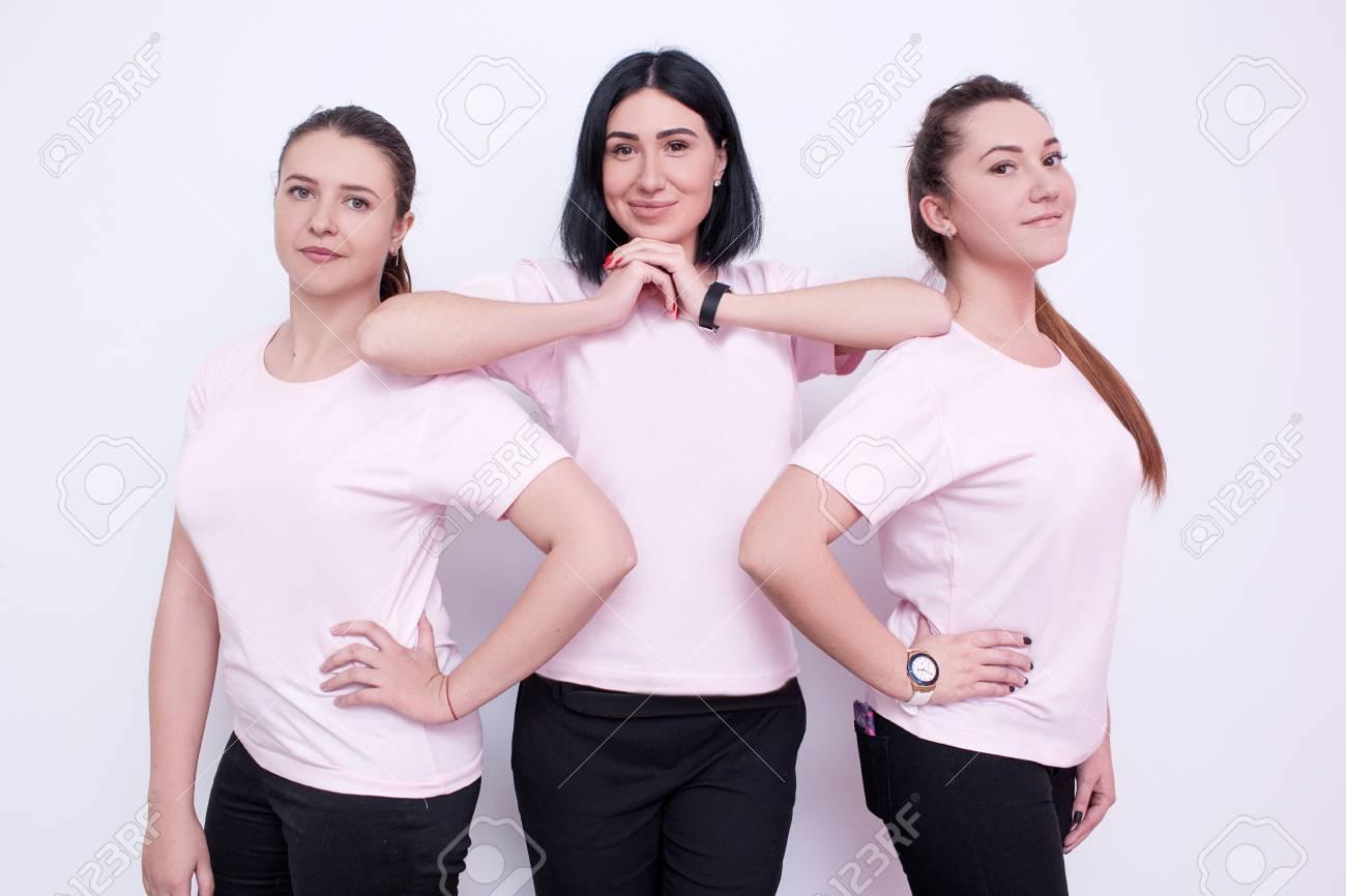 ba683dc87a2 Foto de archivo - Tres mujeres en camisetas blancas. Jóvenes amigos,  publicidad en la ropa, campaña de promoción, azafatas sonrientes, concepto  de equipo ...