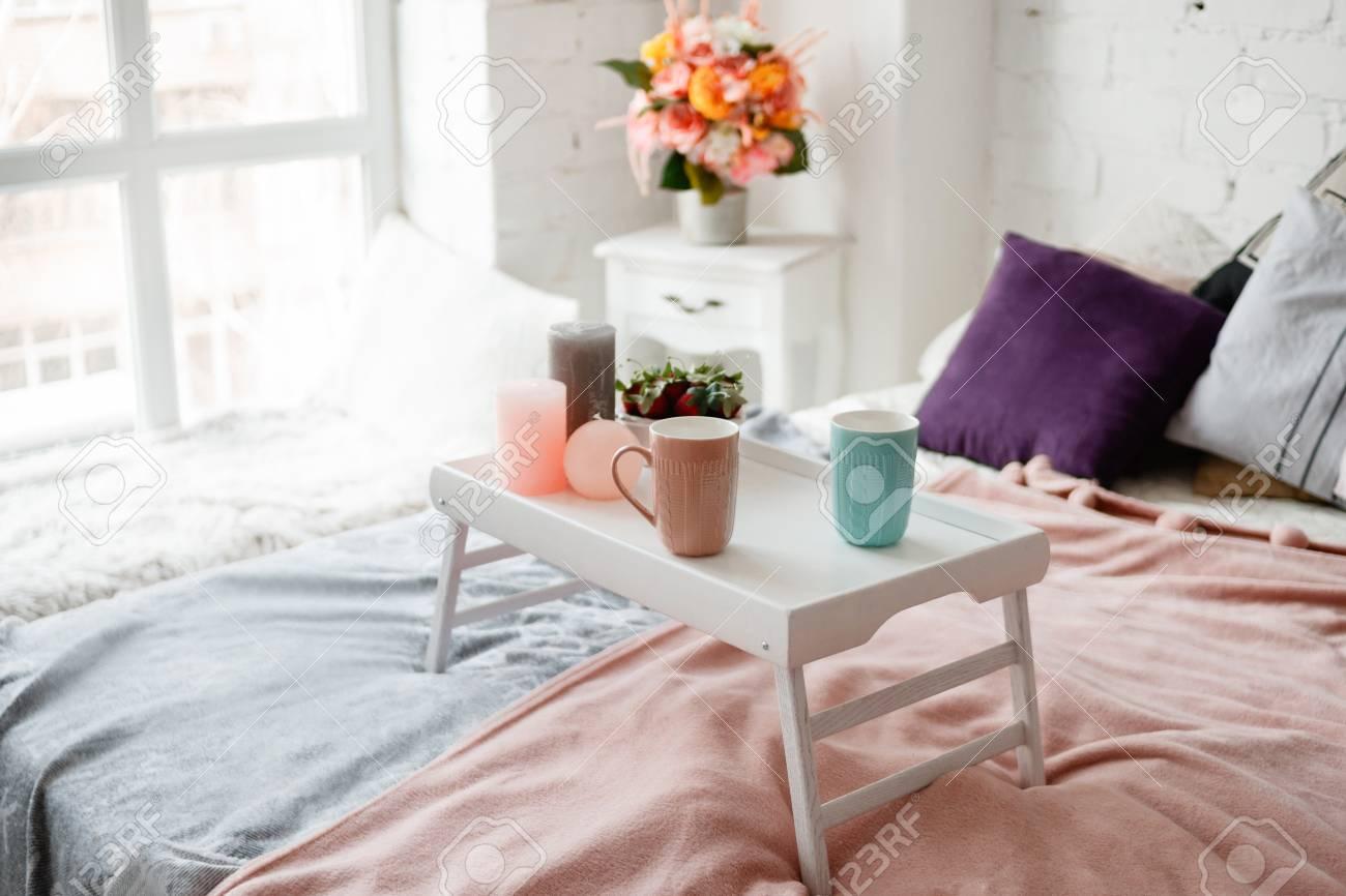 Camera da letto moderna in colori pastello. Il caffè e le fragole sul  piccolo tavolo hanno decorato le candele. Deliziosa colazione a letto,  concetto ...