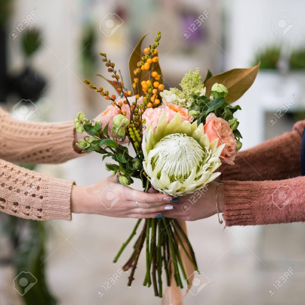Banque d images - Livraison de bouquet de fleurs sûr et rapide pour  quelqu un que vous aimez. Mains de femmes tenant un arrangement créatif de  roses dahlia ... af9f4b749d9c