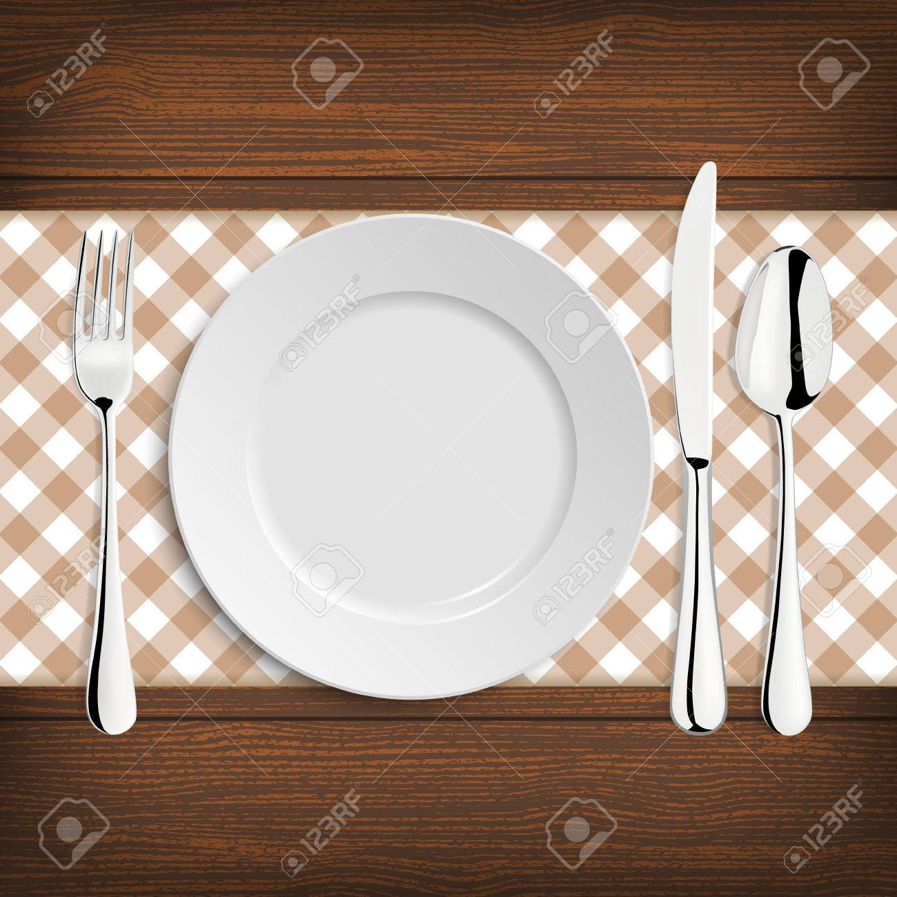 Plate with spoon, knife and fork on a wood table. - 43204198