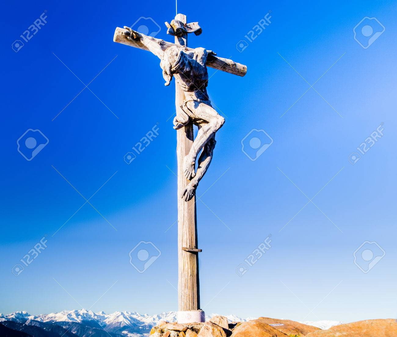 a wood carved statue of the crucifixion of jesus christ on top
