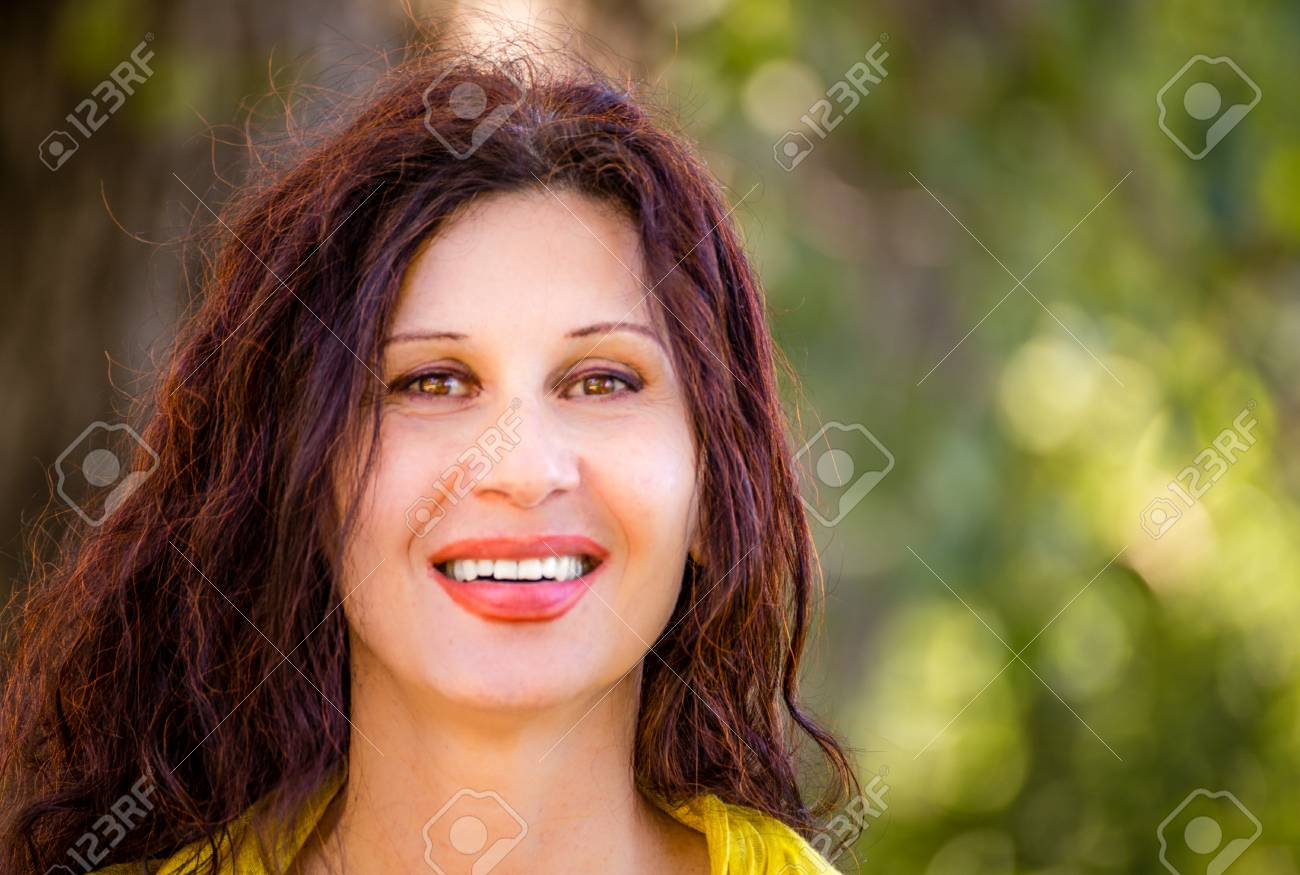 elegant and glamorous mature woman with yellow dress is smiling