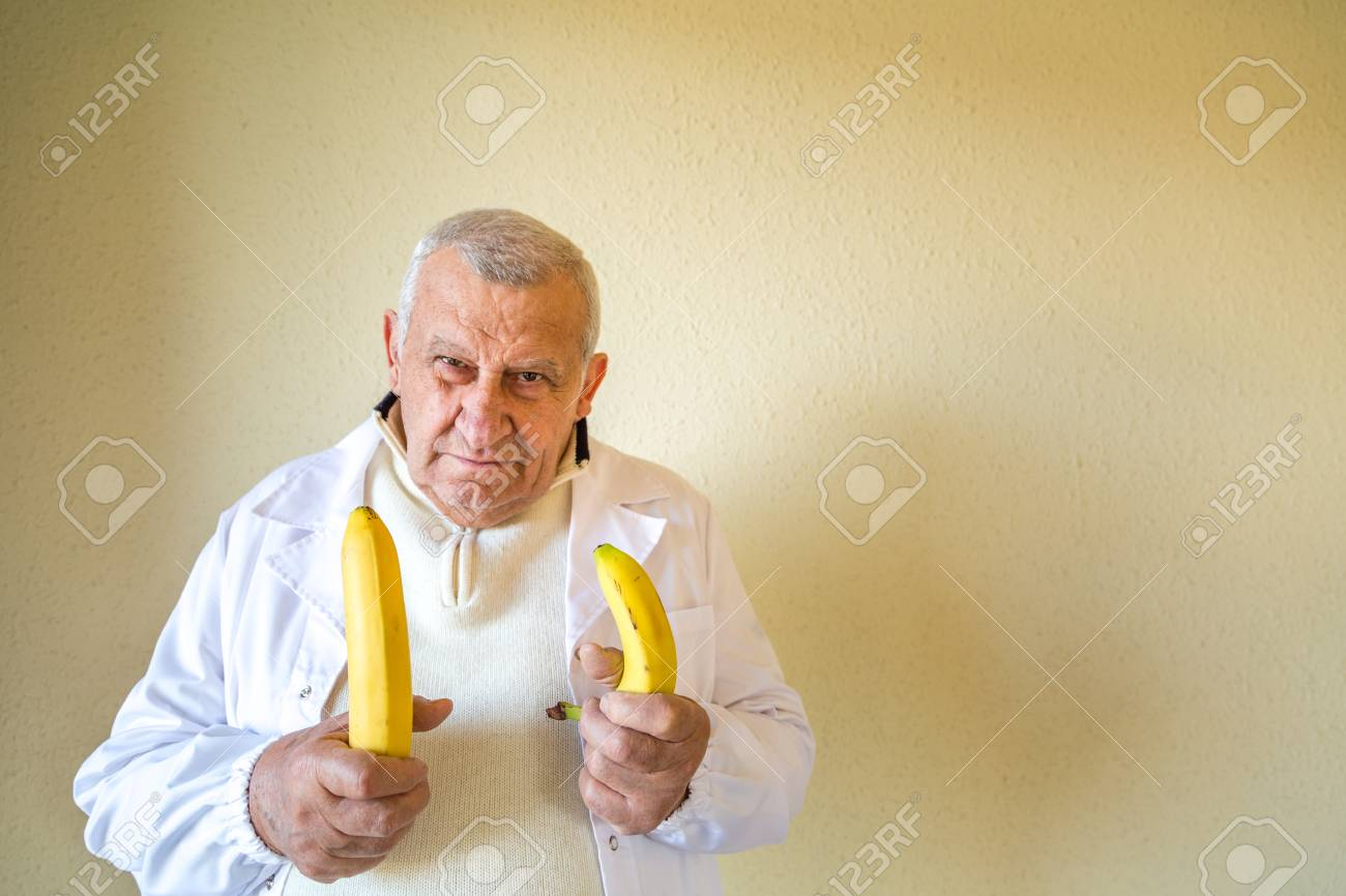 funny faces of old country doctor comparing big banana with small banana as  concept of size