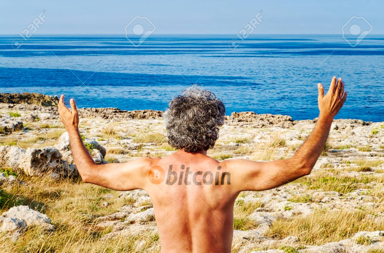 Stock Photo Tatoo Of Public Domain Bitcoin Logo On Back Of Man Raising Hands While Looking To The Horizon Of The Sea