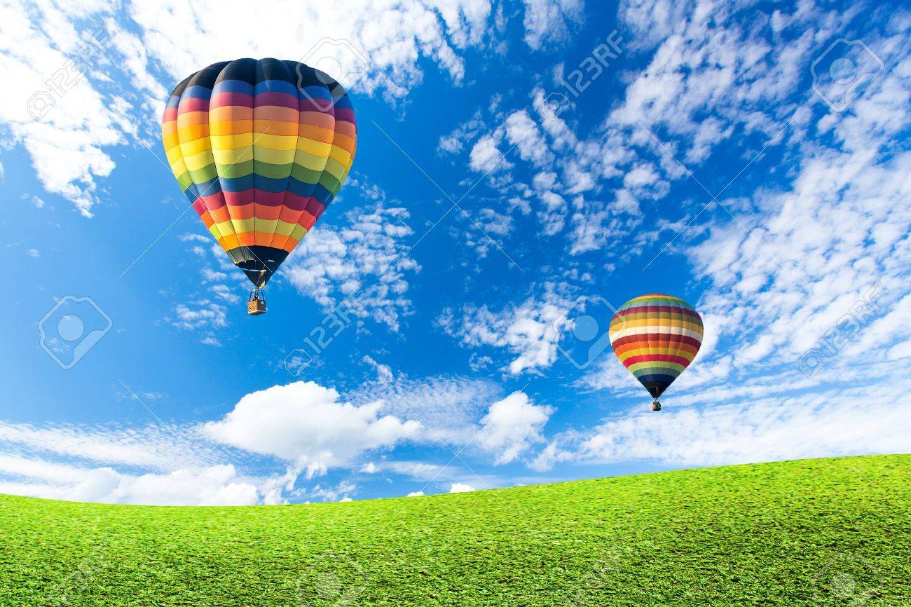 Colorful hot air balloon over green fields - 19722965