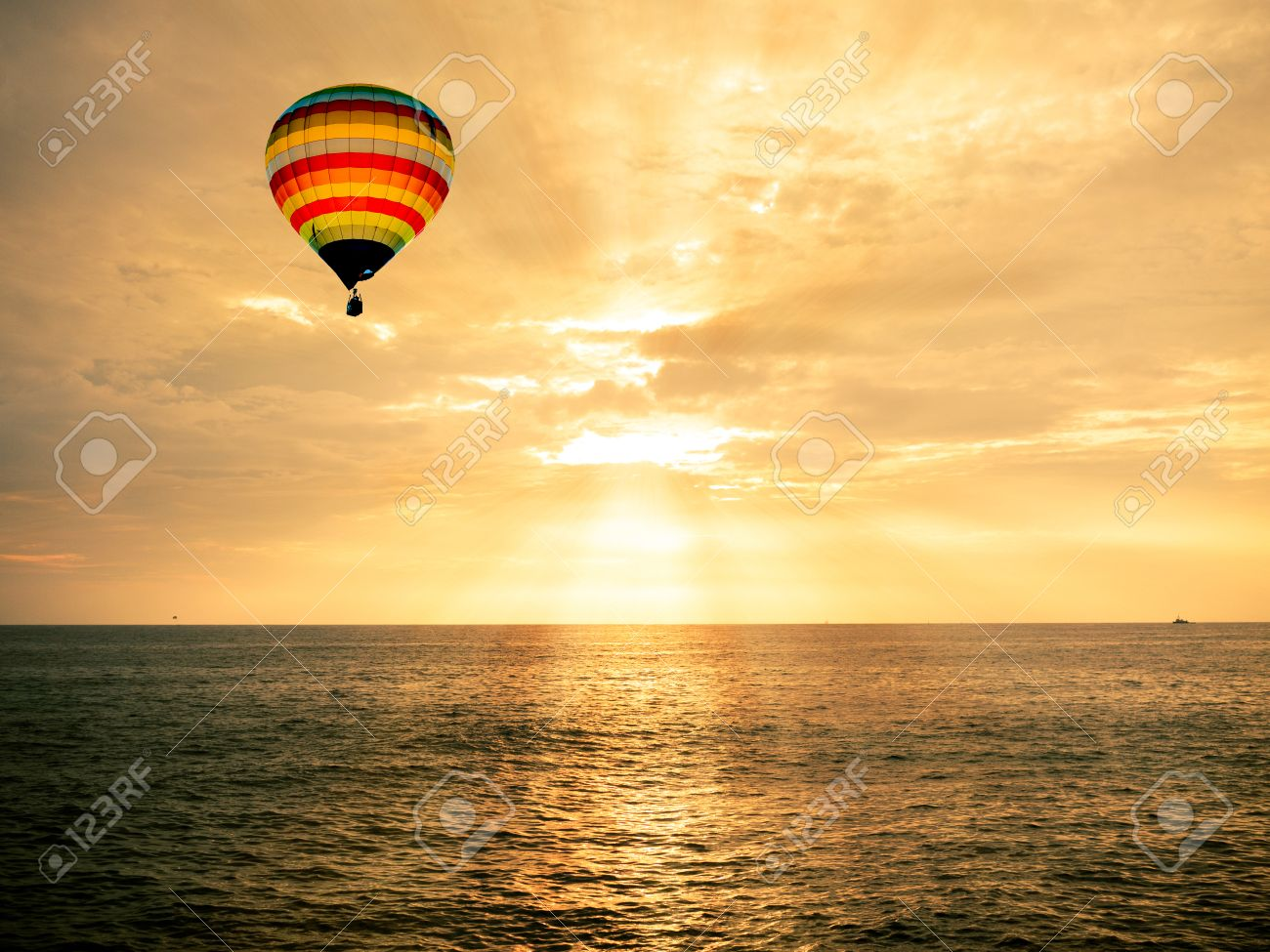 Hot air balloon over the sea at sunset - 32757849