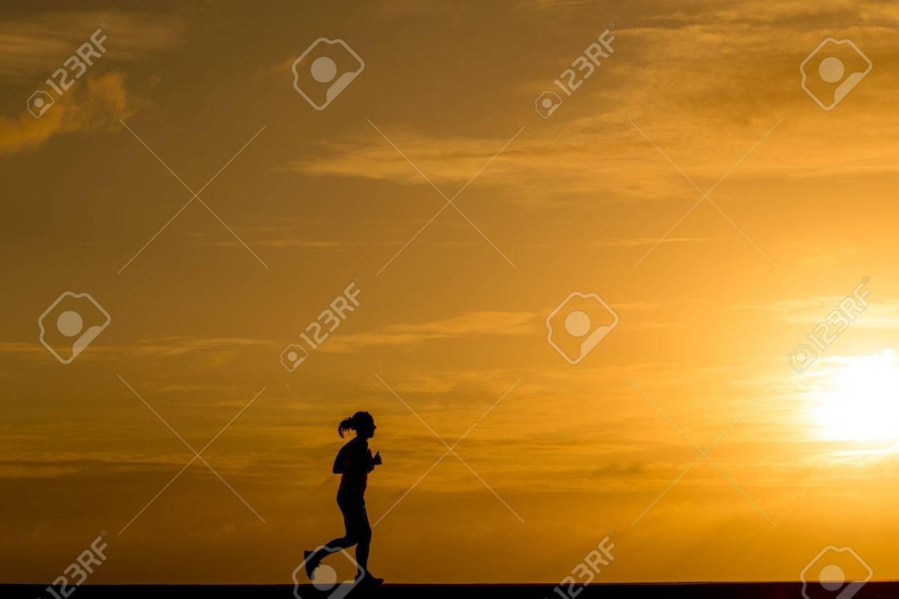 Silhouette women jogging at sunset - 40402663