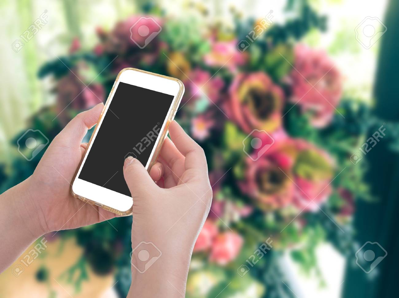 Hand holding mobile phone with flower bouquet background stock photo hand holding mobile phone with flower bouquet background stock photo 56552797 izmirmasajfo