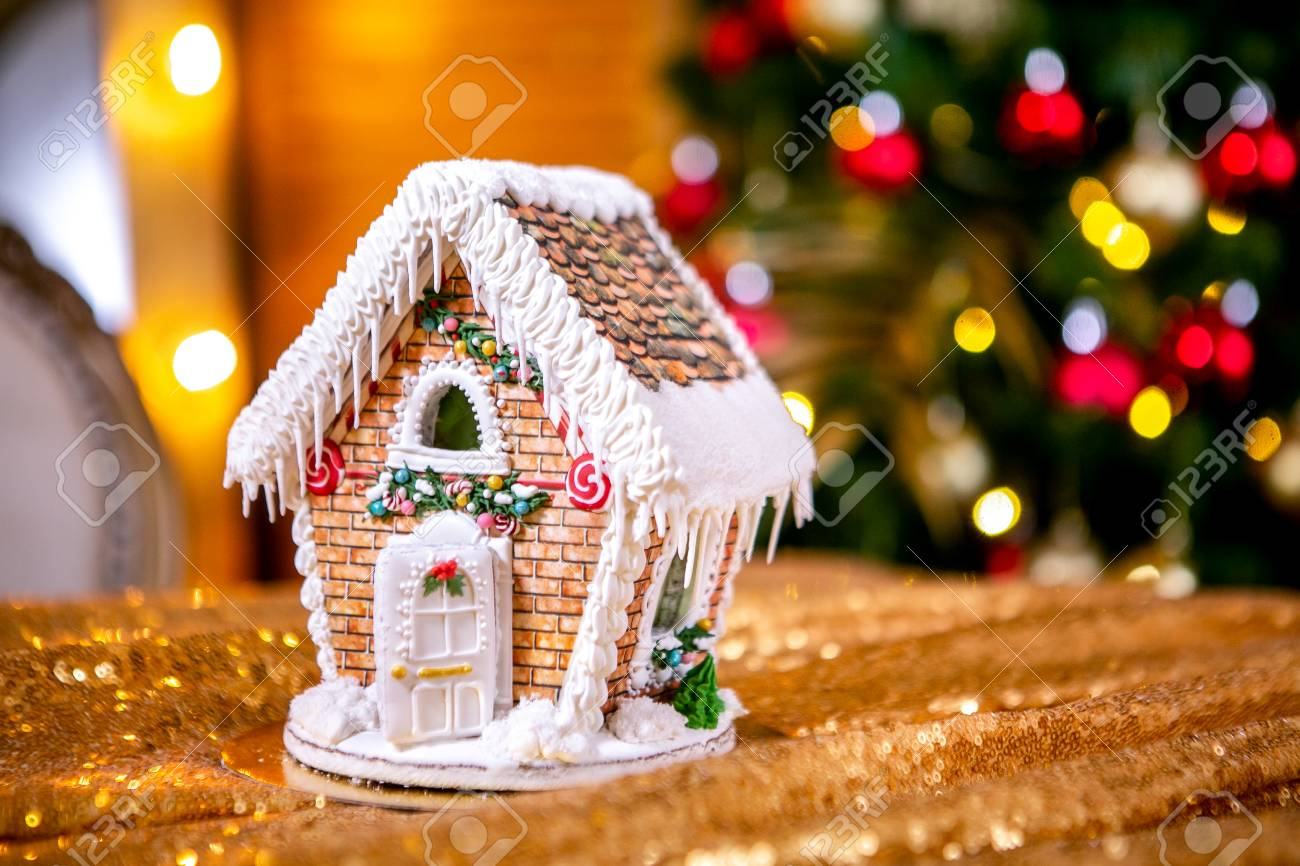 Gingerbread house in front of defocused lights of Christmas decorated..
