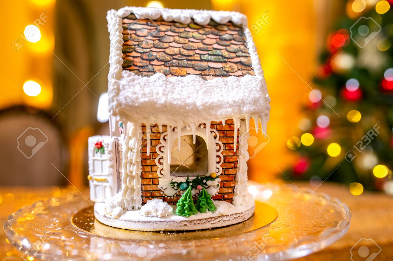 Gingerbread House In Front Of Defocused Lights Of Christmas Decorated