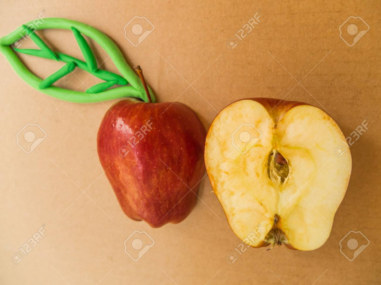 red apple haft with Plasticine green leaf  on isoled brown background Stock Photo - 20644390