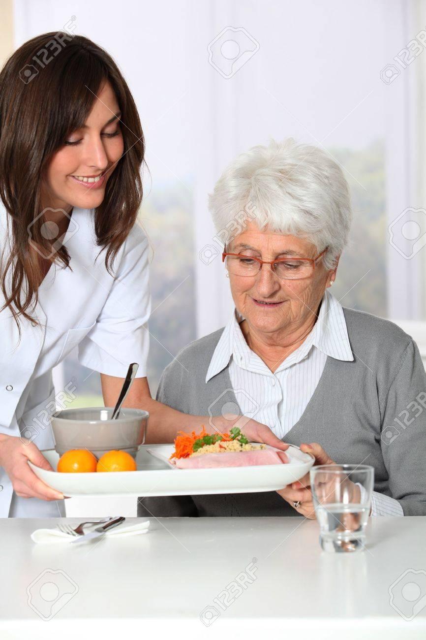 Beautiful nurse bringing meal tray to old woman at nursing home Stock Photo - 8375180