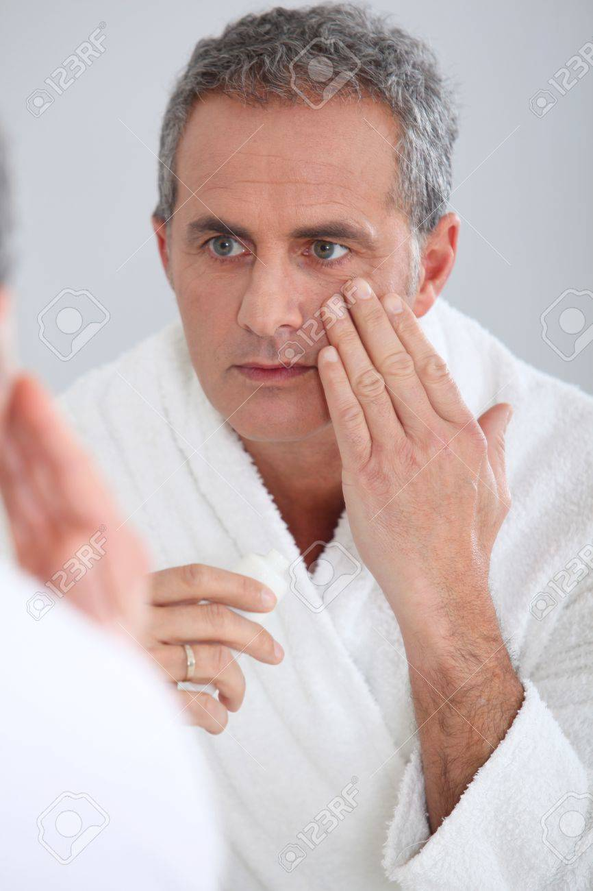 Portrait of mature man applying moisturizer on his face Stock Photo - 8740196