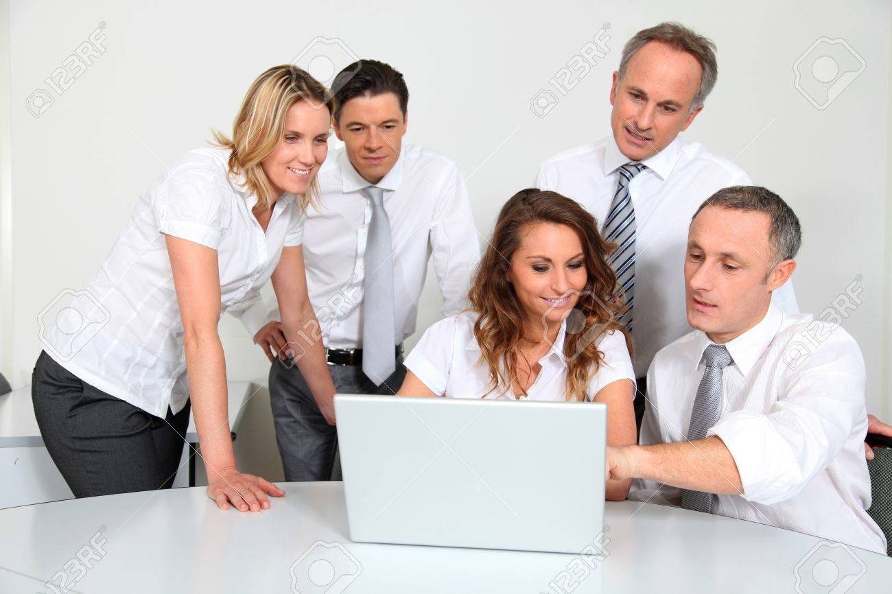Group of office workers in front of laptop computer Stock Photo - 8916226
