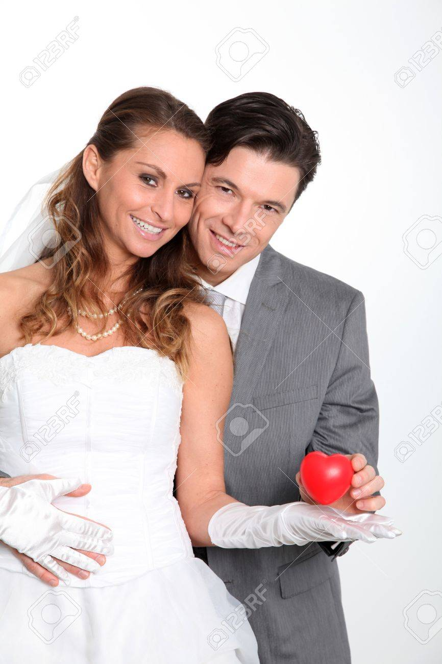 Bride and groom holding red hearts on white background Stock Photo - 9002174