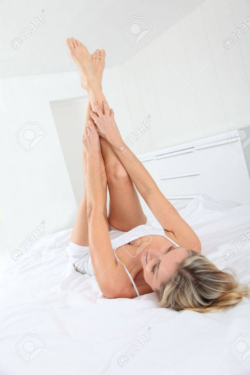 Blond woman laying in bed with legs up Stock Photo - 9004676