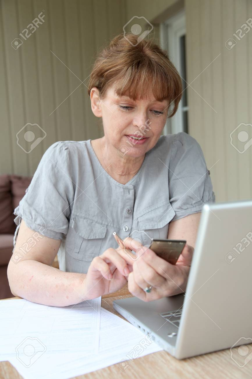 senior woman filling out form with help of internet stock photo