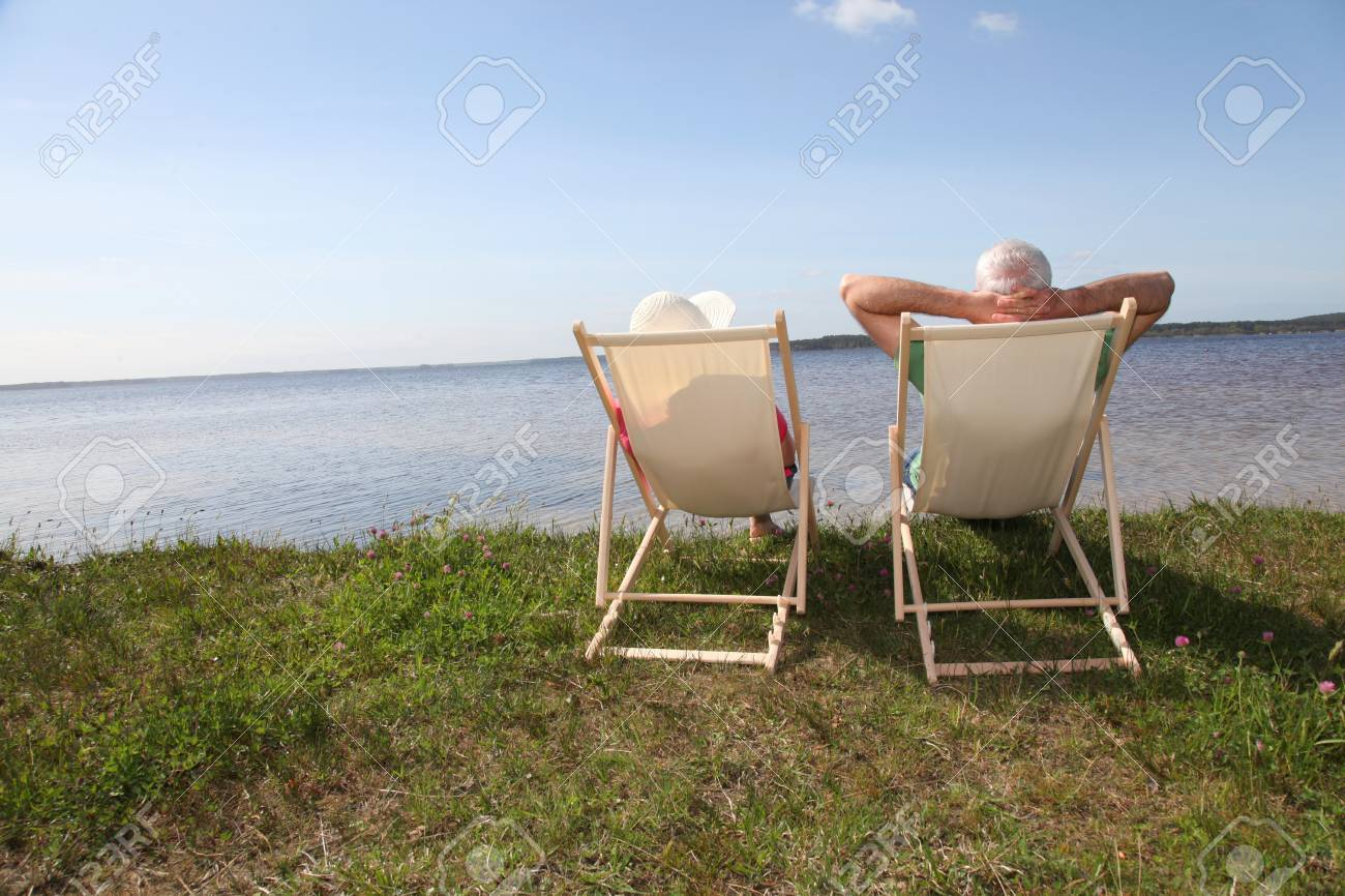 Senior couple in deck chairs in front of a lake Stock Photo - 9480364